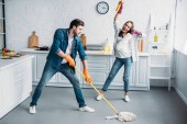 Photo couple in rubber gloves having fun with mop during cleaning kitchen