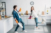 Photo couple in rubber gloves having fun with mop in kitchen
