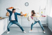 Photo couple having fun and pretending fight with cleaning tools in kitchen