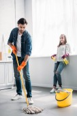 Photo boyfriend cleaning floor in kitchen with mop and girlfriend leaning on kitchen counter