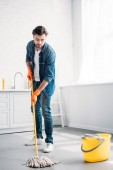 Photo handsome man cleaning floor in kitchen with mop