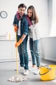 Photo boyfriend cleaning floor in kitchen with mop and girlfriend hugging him