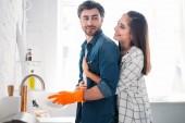 Photo boyfriend washing dishes and girlfriend hugging him in kitchen