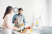 Fotografie girlfriend cutting vegetables and boyfriend adding corn to salad in kitchen