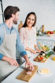 Fotografie smiling couple cooking and cutting vegetables with meat in kitchen