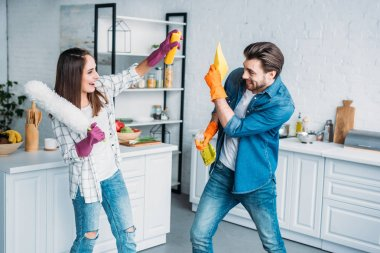 couple having fun during cleaning kitchen and fighting with cleaning tools