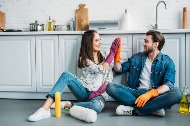 couple sitting on floor and giving high five after cleaning in kitchen