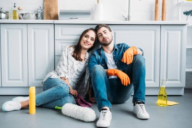 smiling couple sitting on floor and leaning on kitchen counter after cleaning in kitchen