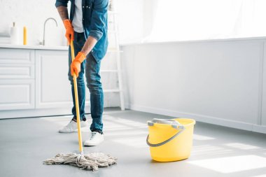cropped image of man cleaning floor in kitchen with mop