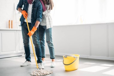 cropped image of boyfriend cleaning floor in kitchen with mop and girlfriend hugging him