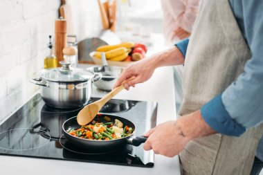 cropped image of boyfriend frying vegetables on frying pan in kitchen