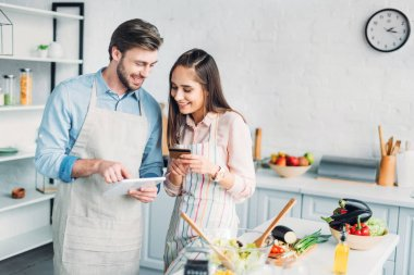 happy couple shopping online with tablet and credit card in kitchen