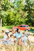happy parents and children spending time at picnic with labrador dog