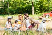 Fotografie happy parents and children spending time at picnic with dog
