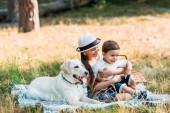 Fotografie glücklich Geschwister sitzen auf Decke bei Picknick mit Labrador Hund