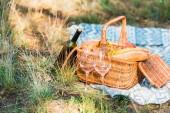 Fotografie láhev na víno, koš s chleby na trávě na pikniku