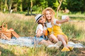 happy mother and daughter taking selfie with smartphone at picnic