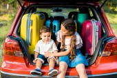 adorable brother and sister sitting near travel bags in car trunk