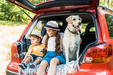 brother and sister sitting on car trunk with labrador dog