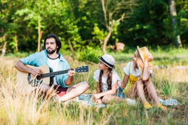 father playing acoustic guitar for daughter and wife at picnic