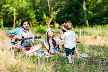 small son taking photo of family with smartphone at picnic