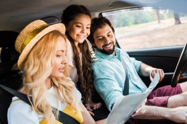 parents and daughter looking at map during traveling by car