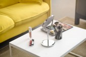 close up view of yellow sofa, mirror, makeup brushes and cosmetics on coffee table