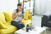 Fotografia giovane donna che applica rossetto mentre si fa il trucco sul divano di casa