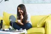 Fotografie usmívající se krásná žena s dlouhými vlasy, při použití prášku na gauči doma při pohledu na zrcadlo