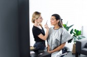 Fotografie side view of makeup artist with brush and attractive woman covered with cloth sitting on chair