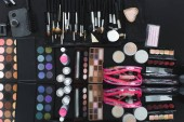 Fotografie top view of arranged various makeup equipment on black tabletop