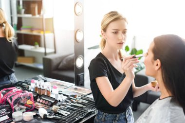 selective focus of beautiful young woman getting makeup done by makeup artist