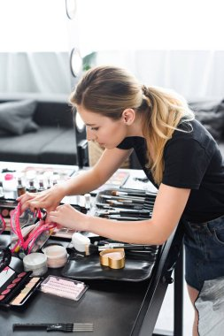 side view of makeup artist searching for cosmetics in beautician during work