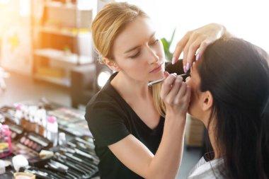 side view of focused makeup artist applying eye shadows on womans eyelid
