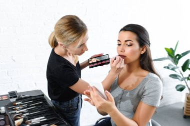 attractive woman using smartphone while makeup artist applying lipstick