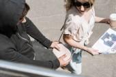 vysoký úhel pohled spuštění žena na ulici s novinami, zatímco muž krádež kabelky