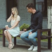Fotografie man pickpocketing wallet from bag of woman with coffee talking on smartphone on bench in park