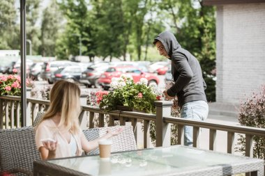 woman looking at robbery stealing her bag on restaurant terrace