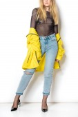 Fotografie cropped shot of young woman in transparent shirt and yellow jacket on white