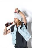 Fotografia uomo in maglia di maschera e denim unicorno maschera lifting e bere rum su bianco