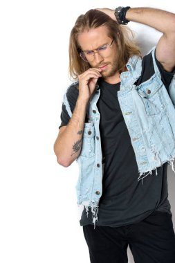 handsome young man in denim vest smoking roll up cigarette on white