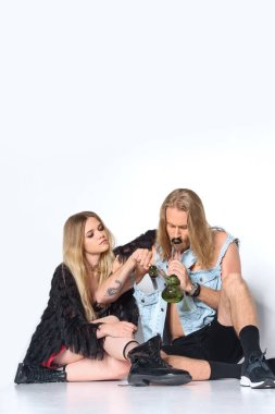 young high couple sitting on floor and smoking water pipe of cannabis on white