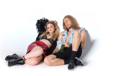 stylish addicted couple sitting on floor with water pipe of cannabis on white