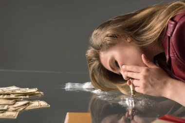 side view of addicted young woman sniffing cocaine from glass table