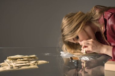 side view of young female junkie sniffing cocaine from glass table