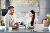 Fotografie side view of smiling couple with newspaper and cup of coffee having conversation at counter with laptop in kitchen