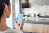 selective focus of woman holding smartphone with skype logo in kitchen