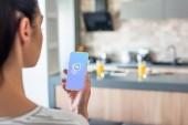 Selektivní fokus ženy držící smartphone s logem shazam na obrazovce v kuchyni