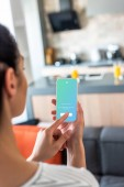 selective focus of woman using smartphone with twitter logo on screen in kitchen
