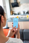 selective focus of woman using smartphone with skype logo in kitchen